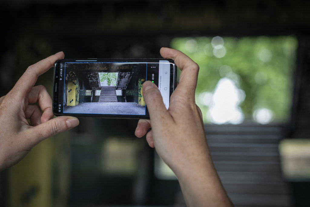 Journalist Alisa Sopova uses the eyeWitness app to photograph the town administration building in Toretsk, Donetsk Oblast, which was destroyed by shelling. Donbass, Eastern Ukraine. 2018. Image credit Anastasia Taylor-Lind